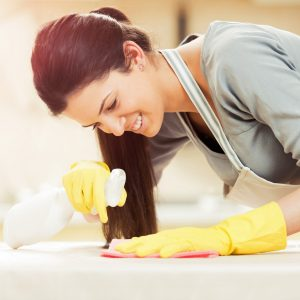 Young woman cleaning a table with sprayer and rag
